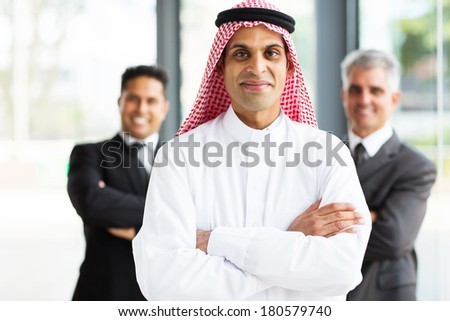 successful arabian businessman in modern office with team