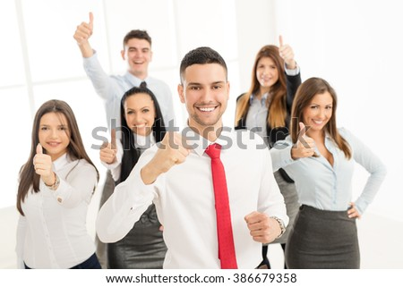 Successful arabian businessman standing proudly with his young business team. They showing thumbs up and looking at camera. - stock photo