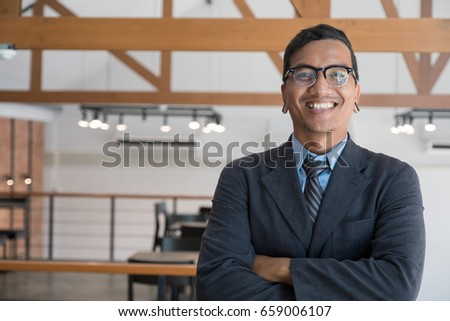 successful asian businessman at workplace. confident young man wearing blue suit standing at office.
