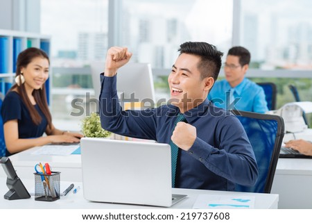 Successful Asian manager with arms up - stock photo