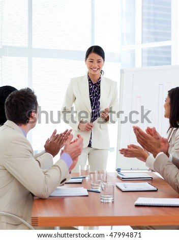 Successful asian woman giving a presentation in a company - stock photo