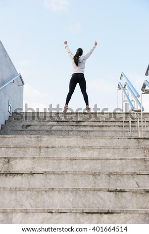 Successful athlete raising arms after running and climbing stairs. Urban fitness woman celebrating sport success and workout goal. - stock photo