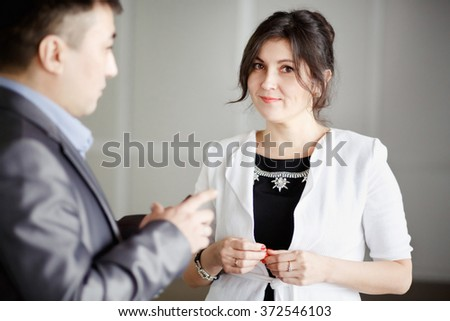 Successful attractive brunette with kind eyes, female employee in office at work talking with chief, during break at work. Wearing white jacket, jewelry. Cute young woman. Subordination, superiors.