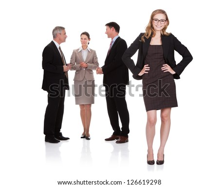 Successful attractive businesswoman standing with her hands on her hips with her team of two business men and a woman standing - stock photo