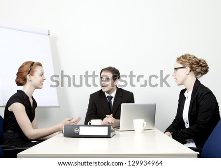 Successful attractive young business team having a meeting seated around a table having an animated discussion as they plan their future strategy