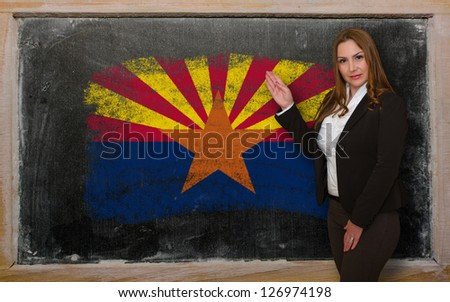 Successful, beautiful and confident woman showing flag of arizona on blackboard for marketing research, presentation and tourist advertising - stock photo