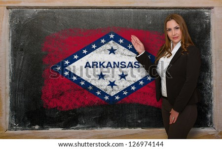 Successful, beautiful and confident woman showing flag of arkansas on blackboard for marketing research, presentation and tourist advertising - stock photo