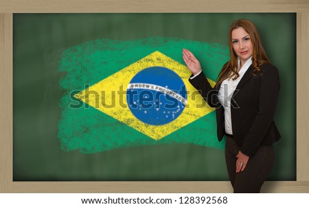 Successful, beautiful and confident woman showing flag of brazil on blackboard for marketing research, presentation and tourist advertising - stock photo