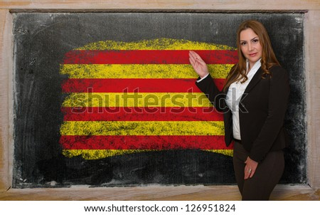 Successful, beautiful and confident woman showing flag of catalonia on blackboard for marketing research, presentation and tourist advertising - stock photo
