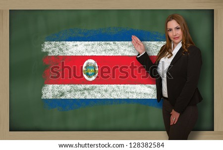 Successful, beautiful and confident woman showing flag of costarica on blackboard for marketing research, presentation and tourist advertising - stock photo
