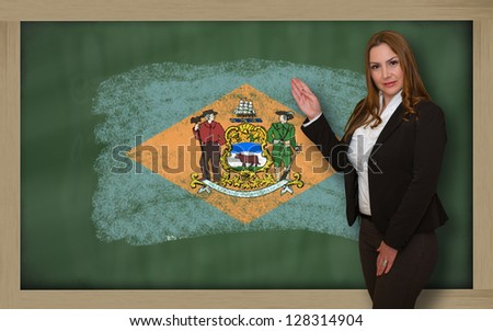 Successful, beautiful and confident woman showing flag of delaware on blackboard for marketing research, presentation and tourist advertising - stock photo