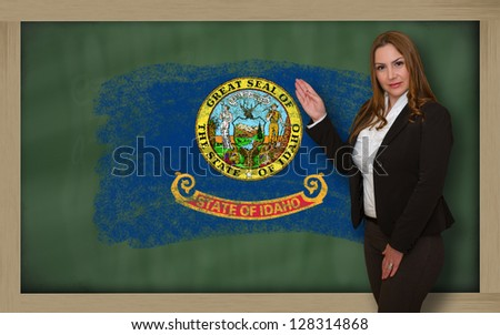 Successful, beautiful and confident woman showing flag of idaho on blackboard for marketing research, presentation and tourist advertising - stock photo