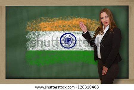 Successful, beautiful and confident woman showing flag of india on blackboard for marketing research, presentation and tourist advertising - stock photo
