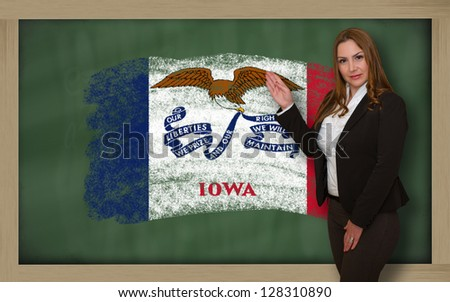 Successful, beautiful and confident woman showing flag of iowa on blackboard for marketing research, presentation and tourist advertising - stock photo