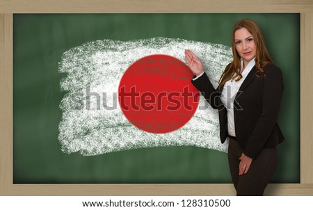 Successful, beautiful and confident woman showing flag of japan on blackboard for marketing research, presentation and tourist advertising - stock photo