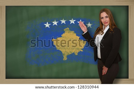 Successful, beautiful and confident woman showing flag of kosovo on blackboard for marketing research, presentation and tourist advertising - stock photo