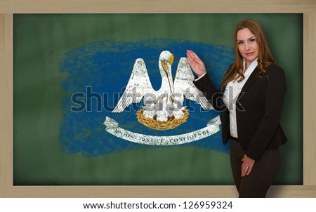 Successful, beautiful and confident woman showing flag of louisiana on blackboard for marketing research, presentation and tourist advertising - stock photo