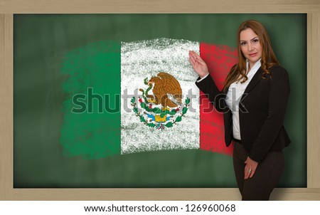 Successful, beautiful and confident woman showing flag of mexico on blackboard for marketing research, presentation and tourist advertising - stock photo