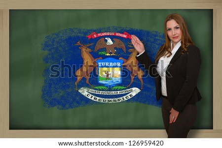 Successful, beautiful and confident woman showing flag of michigan on blackboard for marketing research, presentation and tourist advertising - stock photo