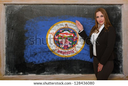 Successful, beautiful and confident woman showing flag of minnesota on blackboard for marketing research, presentation and tourist advertising - stock photo