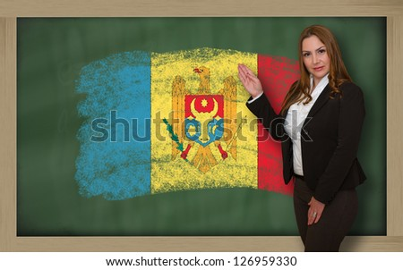 Successful, beautiful and confident woman showing flag of moldova on blackboard for marketing research, presentation and tourist advertising - stock photo