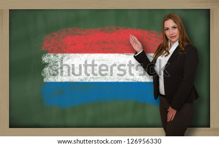 Successful, beautiful and confident woman showing flag of netherlands on blackboard for marketing research, presentation and tourist advertising - stock photo