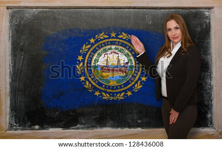 Successful, beautiful and confident woman showing flag of new hampshire on blackboard for marketing research, presentation and tourist advertising - stock photo