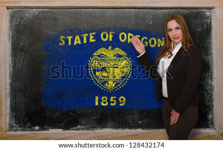 Successful, beautiful and confident woman showing flag of oregon on blackboard for marketing research, presentation and tourist advertising - stock photo