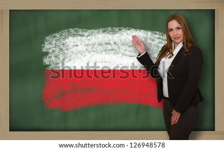 Successful, beautiful and confident woman showing flag of poland on blackboard for marketing research, presentation and tourist advertising - stock photo