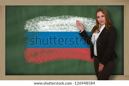 Successful, beautiful and confident woman showing flag of russia on blackboard for marketing research, presentation and tourist advertising - stock photo