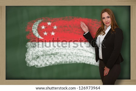 Successful, beautiful and confident woman showing flag of singapore on blackboard for marketing research, presentation and tourist advertising - stock photo