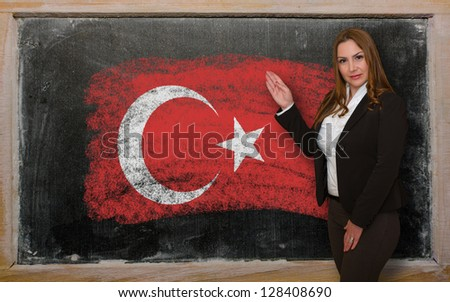 Successful, beautiful and confident woman showing flag of Turkey on blackboard for marketing research, presentation and tourist advertising - stock photo
