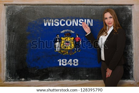 Successful, beautiful and confident woman showing flag of wisconsin on blackboard for marketing research, presentation and tourist advertising - stock photo