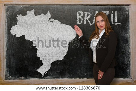 Successful, beautiful and confident young woman showing map of brazil on blackboard for presentation, marketing research and tourist advertising - stock photo