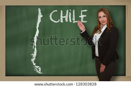 Successful, beautiful and confident young woman showing map of chile on blackboard for presentation, marketing research and tourist advertising - stock photo