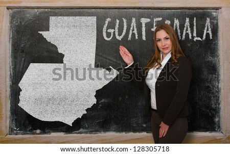 Successful, beautiful and confident young woman showing map of guatemala on blackboard for presentation, marketing research and tourist advertising - stock photo