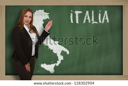 Successful, beautiful and confident young woman showing map of italy on blackboard for presentation, marketing research and tourist advertising - stock photo