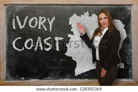 Successful, beautiful and confident young woman showing map of ivory coast on blackboard for presentation, marketing research and tourist advertising - stock photo