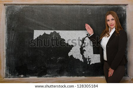 Successful, beautiful and confident young woman showing map of maryland on blackboard for presentation, marketing research and tourist advertising