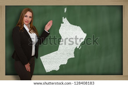 Successful, beautiful and confident young woman showing map of oman on blackboard for presentation, marketing research and tourist advertising