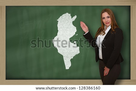 Successful, beautiful and confident young woman showing map of tunisia on blackboard for presentation, marketing research and tourist advertising - stock photo