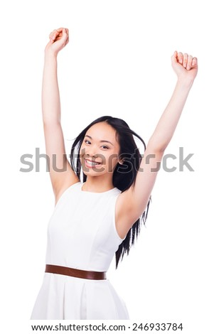 Successful beauty. Beautiful young Asian woman in pretty dress keeping arms raised and smiling while standing against white background   - stock photo