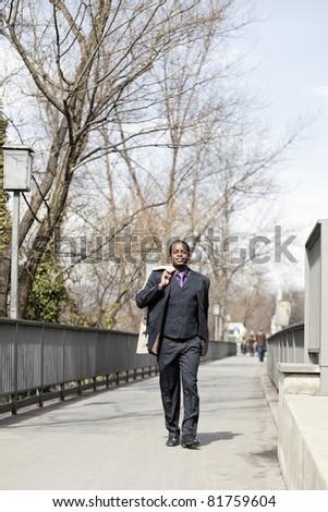 Successful black business man walking on street - stock photo