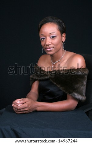 Successful Black woman sitting at a table - stock photo