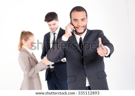 Successful business call. Successful and smiling African businessman talking on a mobile phone showing a thumbs up while his colleagues are working on a tablet in the background
