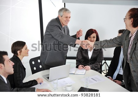 Successful business colleagues shaking hands with eachother at meeting