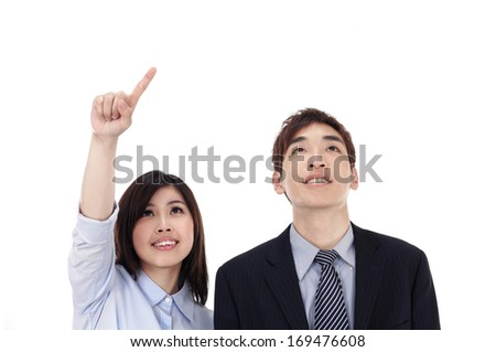Successful business couple pointing away - stock photo
