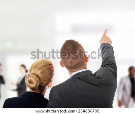 Successful business couple pointing away. - stock photo