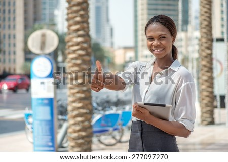 Successful Business Dubai. Smiling African businesswoman businessman holding tablet in hand in Dubai downtown among the skyscrapers showing thumb up and looking at the camera - stock photo