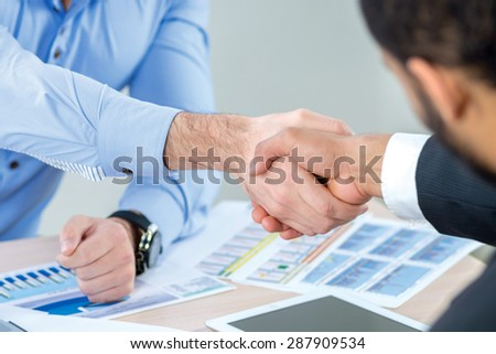 Successful business handshake. Two Confident businessman sitting at the negotiating table in the office and shaking hands close-up view of hands. Business people dressed in formal wear - stock photo